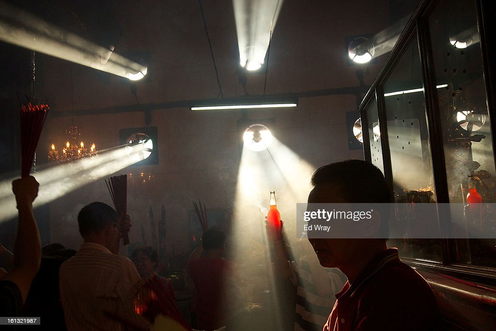 An Indonesian man of Chinese descent holds up a bottle of oil as an offering as he and others pray in the smoke filled Vihara Dharma Bhakti temple on the first day of the Chinese Lunar New year February 10, 2013 in Jakarta, Indonesia. Chinese people around the world are ushering in the Year of the Snake with prayers, feasts and fireworks.