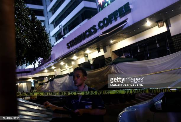 An Indonesian man puts up metalsheets outside the damaged Starbucks coffee shop after a series of explosions hit central Jakarta on January 14 2016 A...