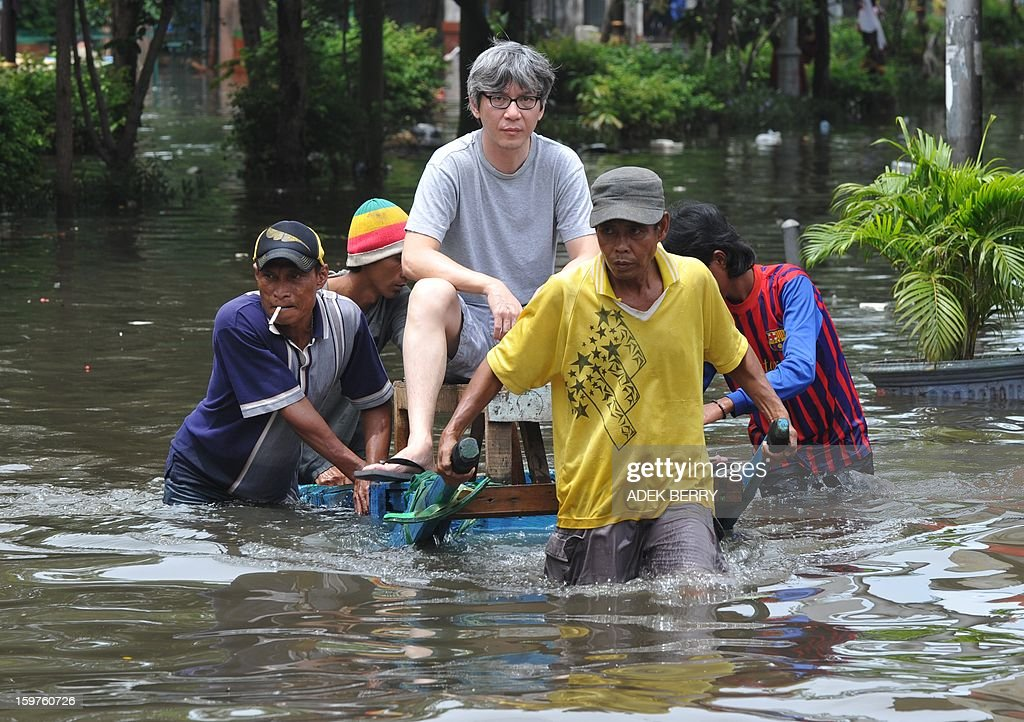 An Indonesian man rides a rental cart pulled by men as they wade down a flooded street in a business centre in Jakarta on January 20, 2013. The death toll from floods in Indonesia's capital Jakarta rose to 15 on January 19 after rescuers found another four bodies. The floods are the worst to hit the capital since 2007 and forced 18,000 people from their homes.