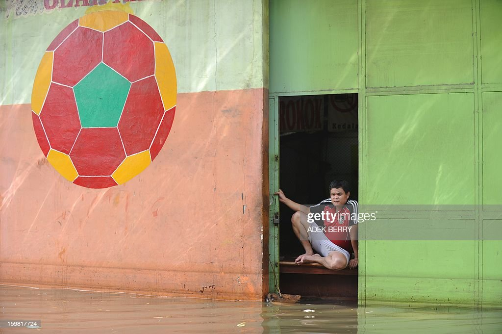 An Indonesian man sits at a sport center inundated by floodwaters in Jakarta on January 21, 2013. Companies and consumers have started to calculate damages and losses from the widespread floods that hit Jakarta on, claiming at least 15 lives a police spokesman said on January 19, displacing thousands from their homes and afflicting capital residents with water-borne illnesses, a local newspaper reported.