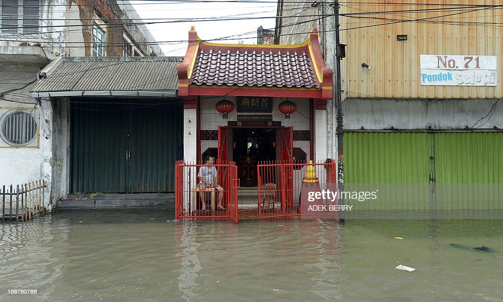 An Indonesian man sits at a temple surrounded by floodwaters in Jakarta on January 20, 2013. The death toll from floods in Indonesia's capital Jakarta rose to 15 on January 19 after rescuers found another four bodies. The floods are the worst to hit the capital since 2007 and forced 18,000 people from their homes.