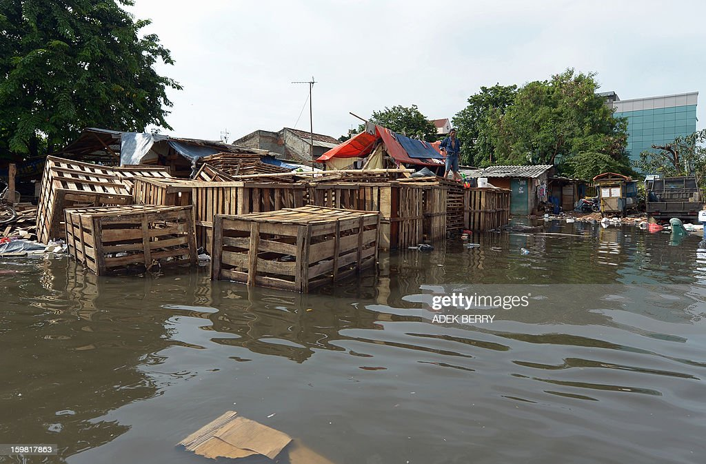 An Indonesian man stands on a wooden structure to stay above floodwaters near his home in Jakarta on January 21, 2013. Companies and consumers have started to calculate damages and losses from the widespread floods that hit Jakarta last week, claiming at least 15 lives, displacing thousands from their homes and afflicting capital residents with water-borne illnesses, a local newspaper reported.