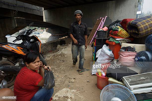 An Indonesian man walks past people sitting with their household goods after being evicted from an illegal housing complex under a highway bridge on...