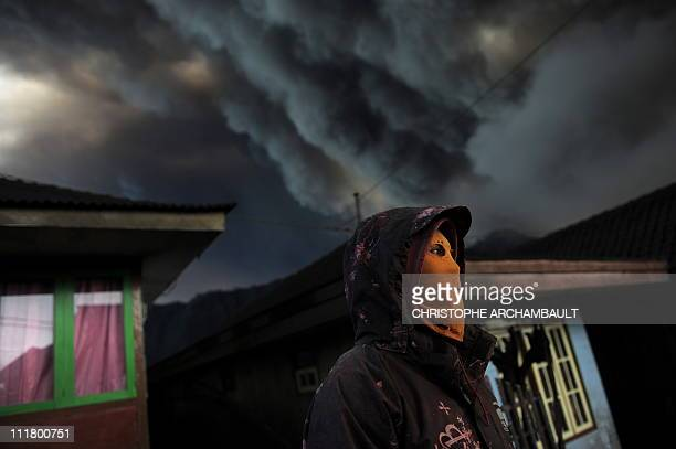 An Indonesian man wears a mask to avoid inhaling ash as he stands in the ashcovered village of Cemoro Lawang near the active Mount Bromo volcano in...