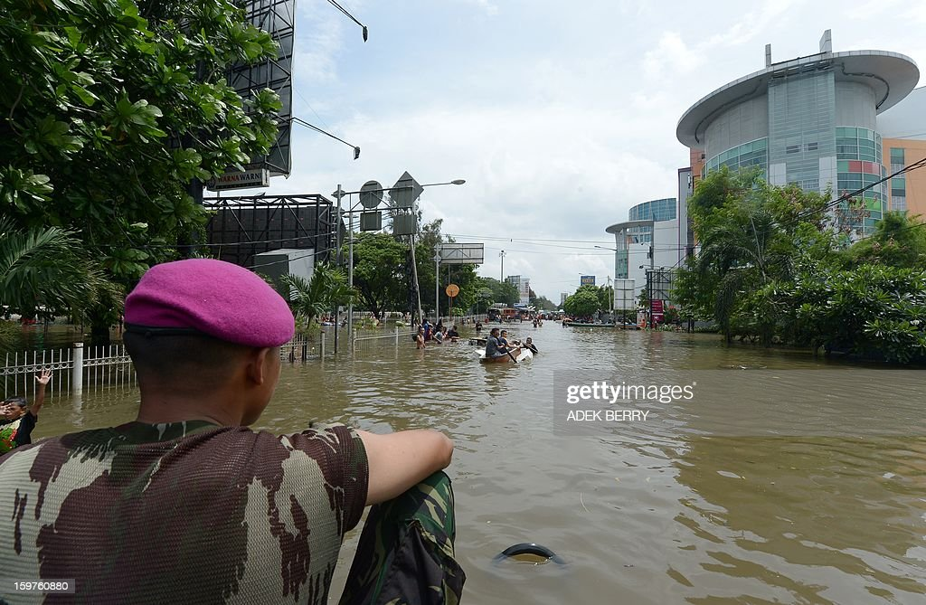 An Indonesian Marine with his team conducts a rescue and evacuation operation at a flooded luxury housing complex in Jakarta on January 20, 2013. The death toll from floods in Indonesia's capital Jakarta rose to 15 on January 19 after rescuers found another four bodies. The floods are the worst to hit the capital since 2007 and forced 18,000 people from their homes.