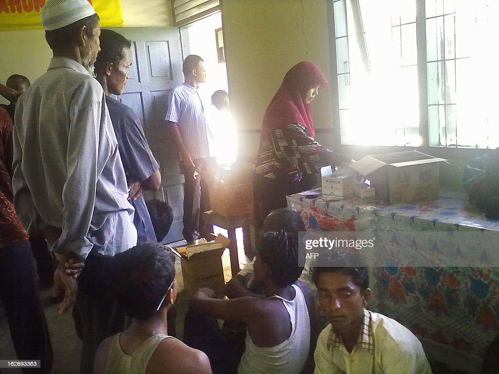 An Indonesian medical staff member (R) attends to a group of ethnic Rohingya asylum-seekers from Myanmar at a government centre in Langsa in Aceh province on March 1, 2013. Fishermen in western Indonesia rescued more than 60 ethnic Rohingya asylum-seekers from Myanmar found adrift in a wooden boat, police said on March 1, in the second such arrival this week.
