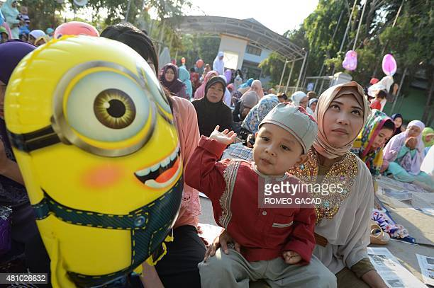 An Indonesian mother prays while her son plays with a balloon during morning prayers for Eid alFitr celebrations at the Sunda Kelapa port in Jakarta...