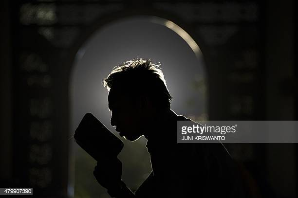 An Indonesian Muslim devotee prays over a Quran as the month of Ramadan continues at a mosque in Surabaya on the eastern Java island on July 8 2015...