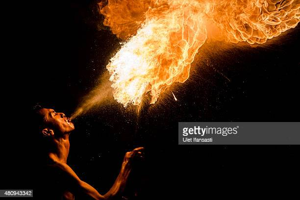 An Indonesian Muslim man breathes fire during a game of fire football known as 'bola api' ahead of Eid AlFitr celebrations on July 16 2015 in...