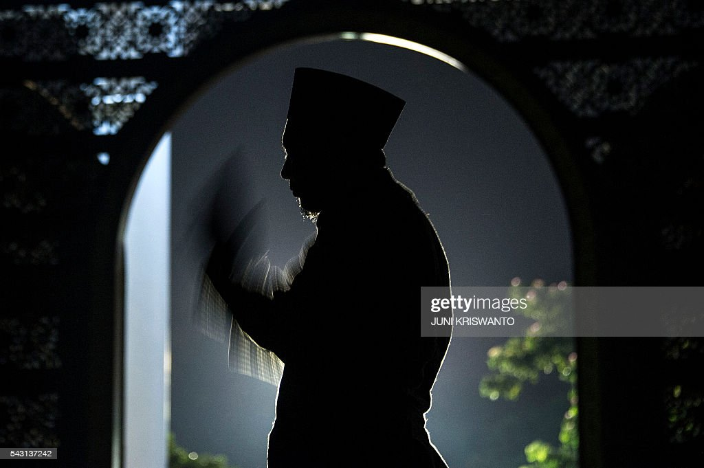 An Indonesian Muslim man offers prayers on the 21th night of holy month of Ramadan at a mosque in the city of Surabaya early on June 26, 2016. Muslims throughout the world are marking the month of Ramadan, the holiest month in the Islamic calendar, during which devotees fast from dawn until dusk. / AFP / JUNI