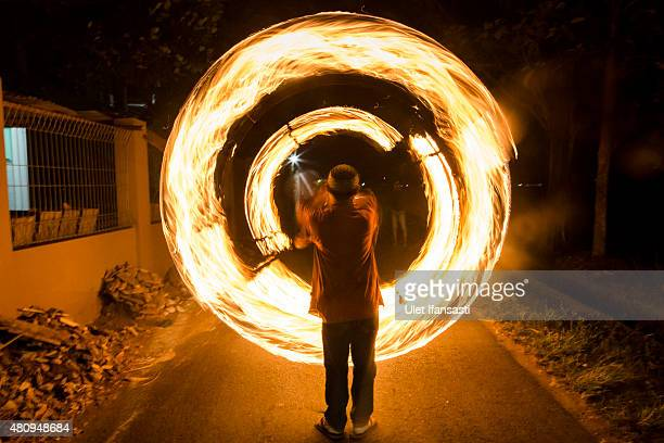 An Indonesian Muslim man plays fire stick during a parade ahead of Eid AlFitr celebrations on July 16 2015 in Yogyakarta Indonesia Muslims will...