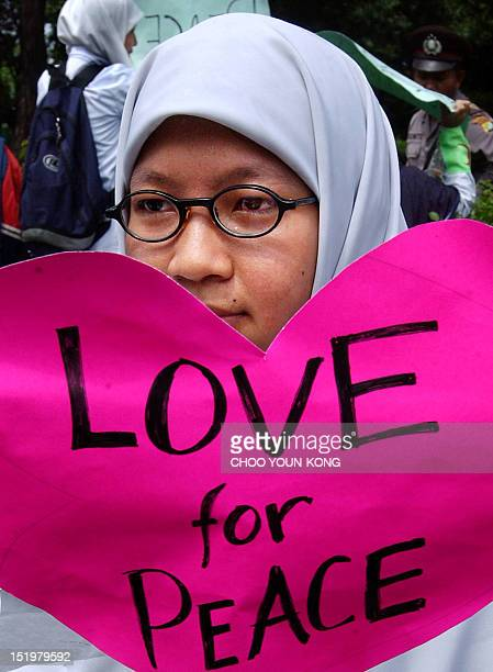An Indonesian Muslim nurse holds an antiwar slogan in Jakarta 15 February 2003 to protest against the US government's plan to attack Iraq About 200...
