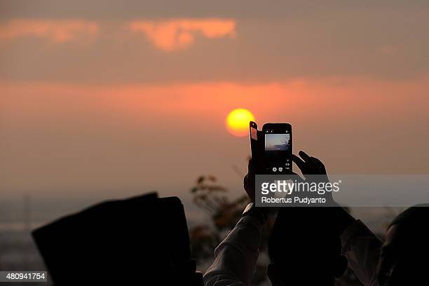 An Indonesian Muslim takes photos with a smartphone during Rukiyatul Hilal to see the new crescent moon that determines the end of Ramadan at Condro...