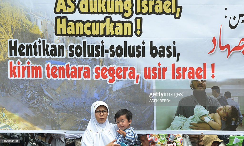 An Indonesian Muslim woman with her child stand next to a banner that reads 'The US supports Israel, Destroy! Stop lip service solution, send troops soon, oust Israel' during a protest against the Israel and US governments and against fresh Israeli air strikes on the Gaza Strip, outside the US embassy in Jakarta on November 19, 2012. Indonesia, the world's most populous Muslim nation, with 240 million people, is a strong supporter of the Palestinian cause. AFP PHOTO / ADEK BERRY