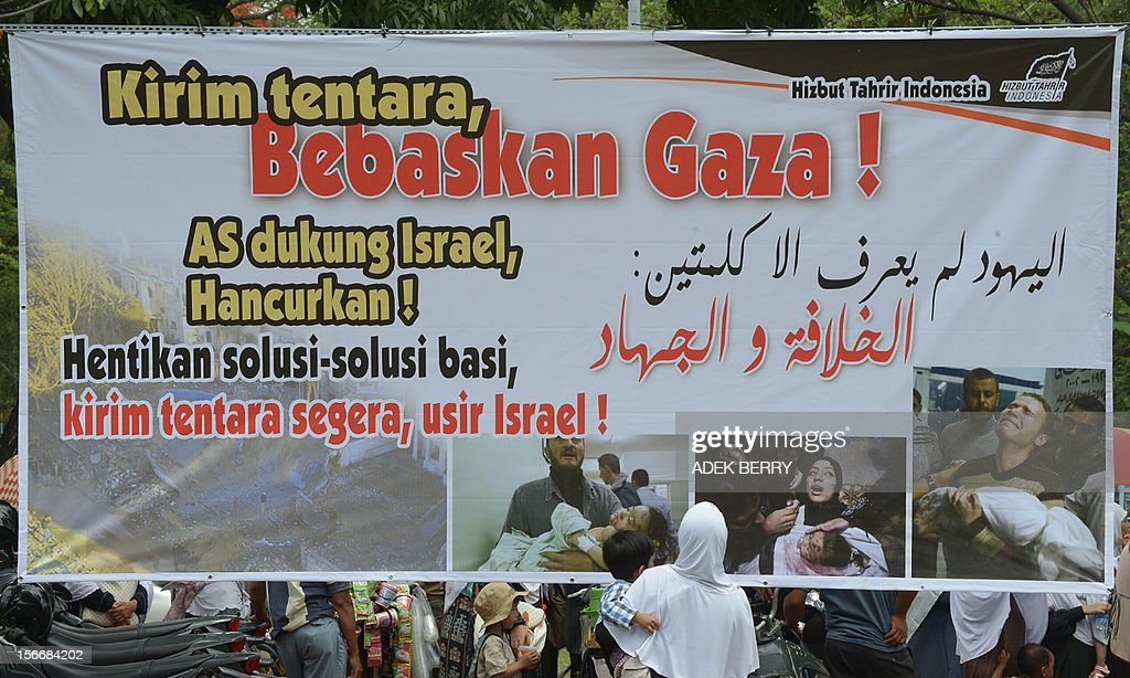 An Indonesian Muslim woman with her child stand next to a banner that reads 'The US supports Israel, Destroy! Stop lip service solution, send troops soon, oust Israel' during a protest against the Israel and US governments and against fresh Israeli air strikes on the Gaza Strip, outside the US embassy in Jakarta on November 19, 2012. Indonesia, the world's most populous Muslim nation, with 240 million people, is a strong supporter of the Palestinian cause.