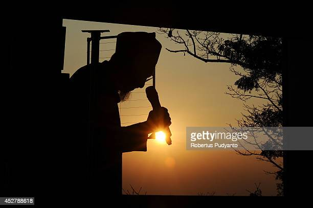 An Indonesian Muslims speaks during a Rukyatul Hilal to see the new crescent moon which determines the end of Ramadan at Condro Dipo Hill on July 27...