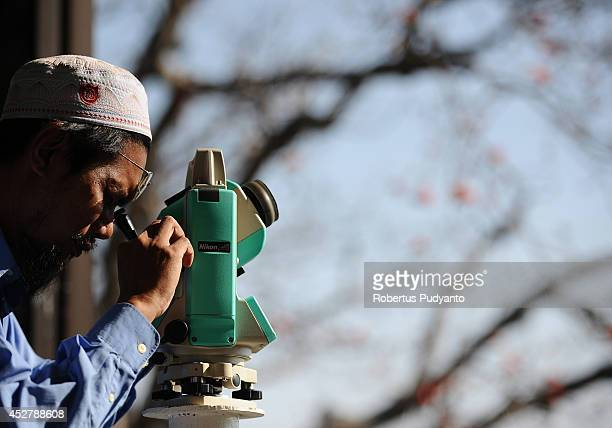 An Indonesian Muslims uses a telescope to hold a Rukyatul Hilal to see the new crescent moon that determines the end of Ramadan at Condro Dipo Hill...
