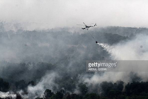 An Indonesian national board for disaster management MI17 helicopter waterbombs a fire spot over Ogan Komering Ilir area in South Sumatra province on...