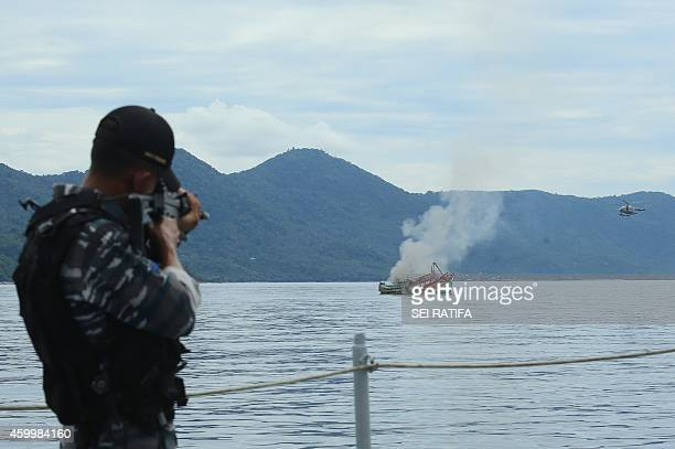 An Indonesian Navy officer targets a Vietnam boat fishing to sink held due to illegal fishing activities in Indonesia water on Anambas island Riau...