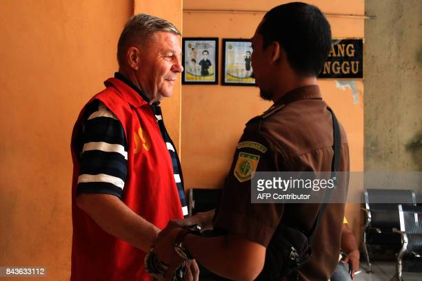 An Indonesian officer removes the handcuffs off Italian Bruno Gallo at a court in Mataram on September 7 2017 An elderly Italian man has been jailed...