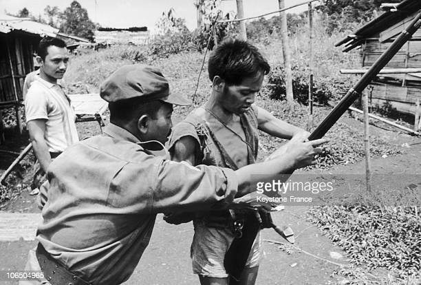An Indonesian Officer Showing A Dayak How To Hold A Shotgun During A Hunt For Guerrilla Communists In Borneo On December 5Th 1968