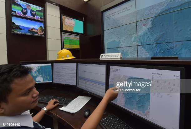 An Indonesian official at Indonesia's Meterological Climatological and Geophysical Agency in Jakarta points to a computer screen showing a map of...