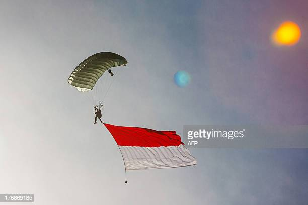 An Indonesian paratrooper flies the Indonesian national flag during the 68th independence day celebrations in Banda Aceh Northern Sumatra island on...