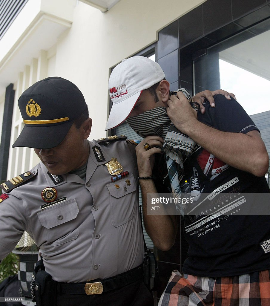 An Indonesian policeman escorts an illegal immigrant at Surabaya police station in East Java on March 15, 2013. 80 immigrants from Iran and Iraq were arrested in Tuban as they were traveling on a bus and in an SUV. Indonesia is used as a transit hub, where potential immigrants pay people-smugglers for passage on leaky wooden vessels after fleeing their home countries. AFP PHOTO / Juni KRISWANTO
