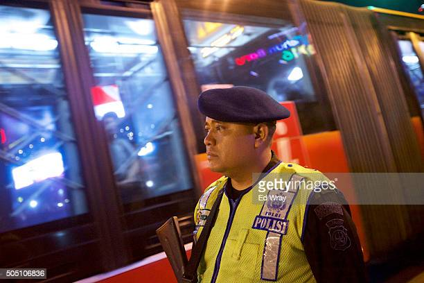 An Indonesian policeman guards a street as a city bus passes near the site of yesterday's terrorist attack during a 'We Are Not Afraid' rally on...