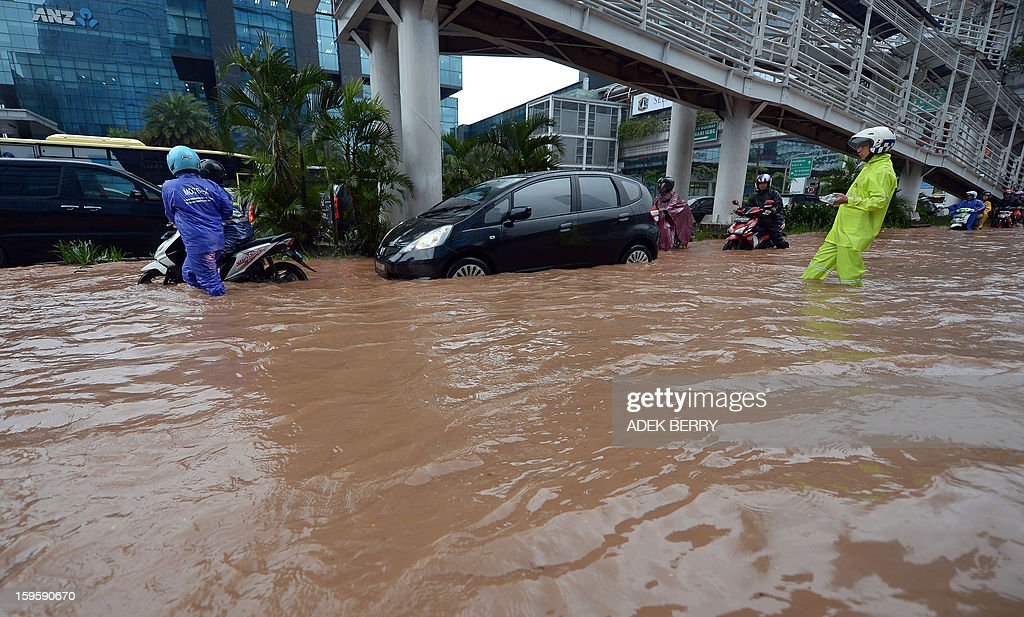 An Indonesian policeman (R) manages traffic as motorists try to navigate through a flooded main street in Jakarta on January 17, 2013. Severe flooding following torrential rain has driven almost 10,000 people from their homes in the Indonesian capital, an official said on January 16, with two people killed so far in the seasonal chaos. AFP PHOTO / ADEK BERRY