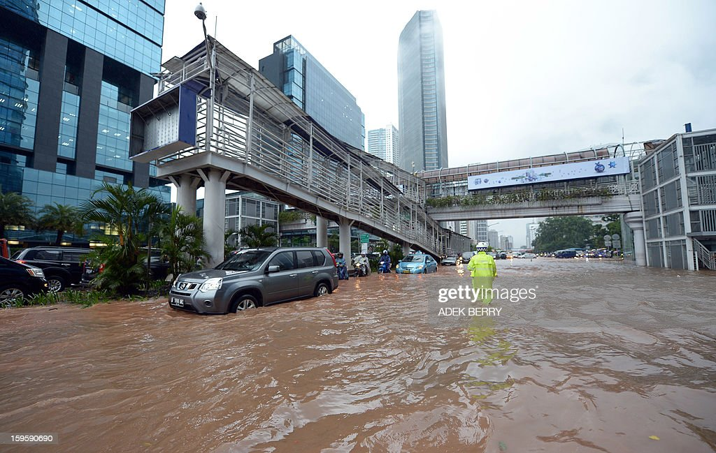An Indonesian policeman (R) manages traffic as motorists try to navigate through a flooded main street in Jakarta on January 17, 2013. Severe flooding following torrential rain has driven almost 10,000 people from their homes in the Indonesian capital, an official said on January 16, with two people killed so far in the seasonal chaos.