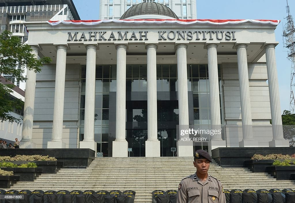 An Indonesian policeman stands guard outside the Constitutional Court in Jakarta on August 20, 2014, as authorities increase the security ahead of the announcement on August 21 of its decision about the presidential election dispute. Indonesian ex-general Prabowo Subianto angrily claimed widespread cheating cost him victory in the country's presidential election at the start of legal challenge to the results on August 6. Prabowo, a controversial former military figure with roots in the era of dictator Suharto, also declared victory at the July 9 presidential election, but official results two weeks later confirmed Joko Widodo won a decisive victory. AFP PHOTO / ADEK BERRY