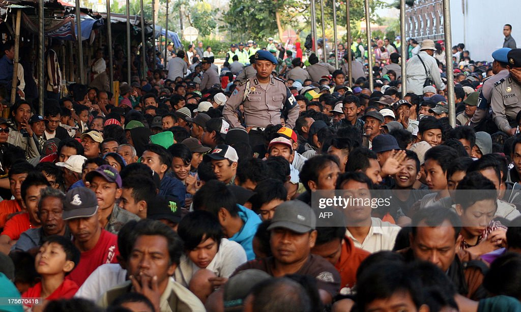 An Indonesian policeman (C) watches over hundreds of people waiting to receive 'zakat', or alms, given to poor people during Ramadan at a tabacco factory of Gudang Garam, Indonesia's biggest clove cigarette manufacturer, in Kediri in East Java province on August 6, 2013. Each person received 10,000 (1 USD) or up to 20,000 rupiah (2 USD) cash from company in a tradition of giving charity to the poor during Islam's holy month of Ramadan.