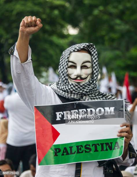 An Indonesian protester gestures and while holding a placard calling for freedom to Palestine during a protest in front of the US consulate general...