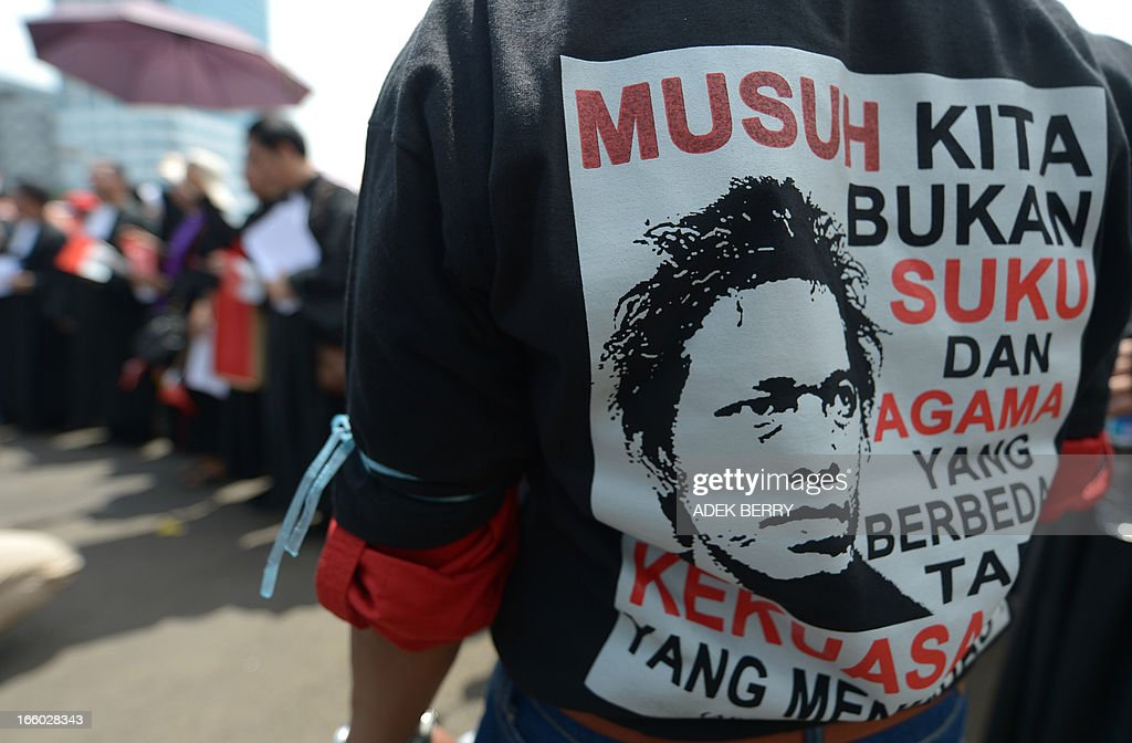 An Indonesian protester (R) wears a T-shirt that reads, 'Our enemy is not the diversity of faiths or races but an oppresive government' during a protest against Indonesian government failures to guarantee freedom of religion in Jakarta on April 8, 2013. Around 200 Indonesian minority leaders protested against religious intolerance and discrimination in the Muslim-majority country. The group representing Christians, Ahmadiyah and Shiite Islamic minority sects gathered outside the parliament, singing the country's national anthem and shouting 'We have rights' and 'Stop intolerance'.