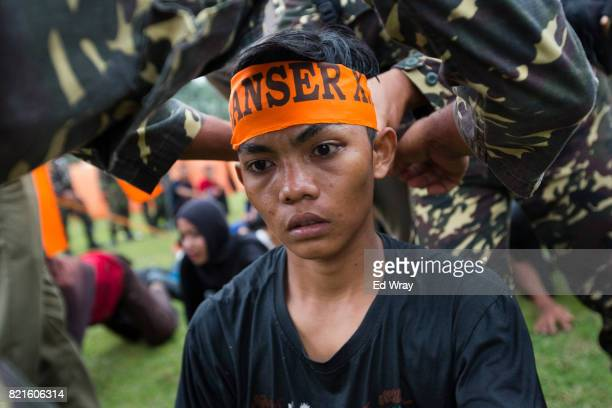 An Indonesian recruit kneels as a Banser Headband is tied to his head at the start of three day induction course on July 21 2017 in Kebumen Indonesia...