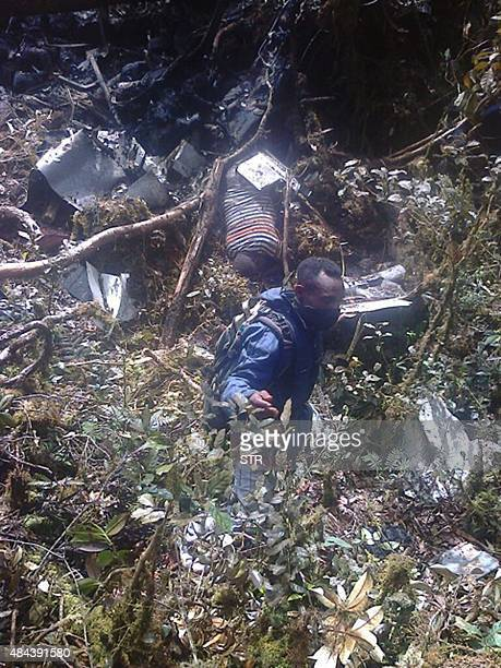 An Indonesian rescuer searches through the wreckage of the Trigana Air ATR 42300 twinturboprop plane at the crash site in the mountainous area of...