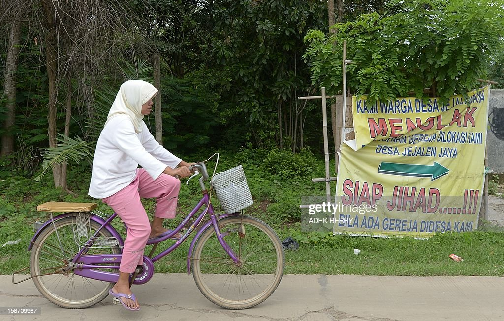 An Indonesian resident cycles past a banner that reads 'Residents of Jejalen Jaya reject the construction of a church here, Ready for Jihad if there is a church in our village' next to a piece of land owned by a Christian congregation from the Filadelfia Batak Christian Protestant church in Bekasi on December 25, 2012. More than 200 Indonesian Muslims threw rotten eggs at Christians wanting to hold a Christmas mass near land outside Jakarta where they plan to build a church, police and a witness said.