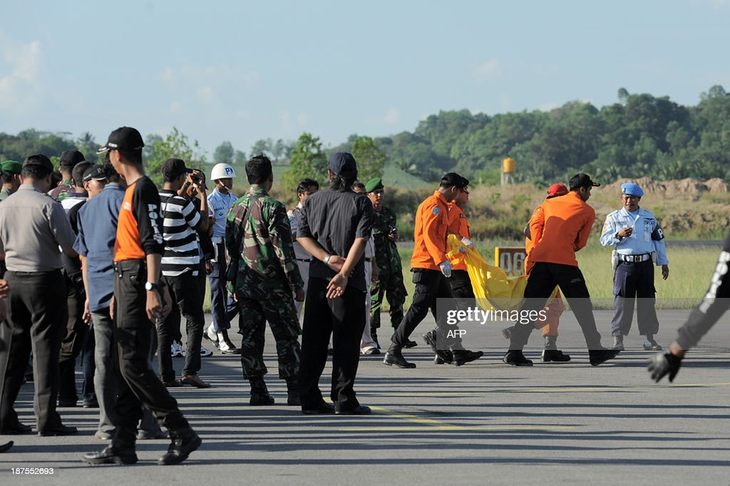 An Indonesian search and rescue team carry a victim's body from a helicopter crashed that killed 13 people, at Tarakan military airport in Tarakan on November 10, 2013. Thirteen people died when an Indonesian army helicopter carrying construction workers to build a military outpost crashed in the jungles of Borneo on November 9 and burst into flames, an official said.