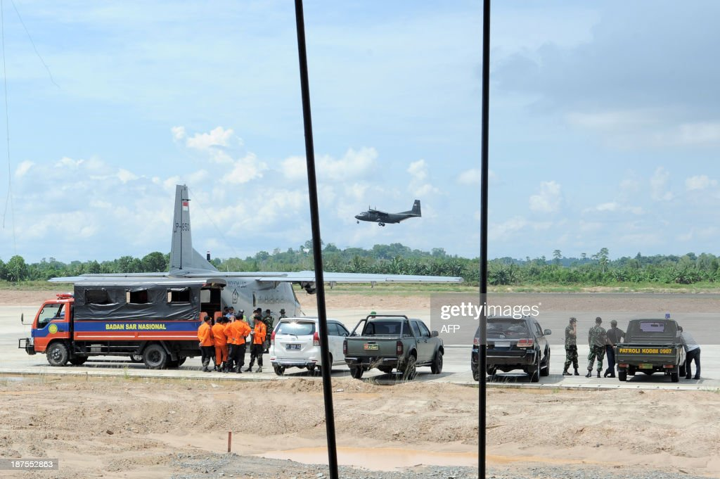 An Indonesian search and rescue team wait while others carry out the evacuation of victims of an army helicopter that crashed in Northern Kalimantan, at Tarakan military airport in Tarakan on November 10, 2013. Thirteen people died when an Indonesian army helicopter carrying construction workers to build a military outpost crashed in the jungles of Borneo on November 9 and burst into flames, an official said.