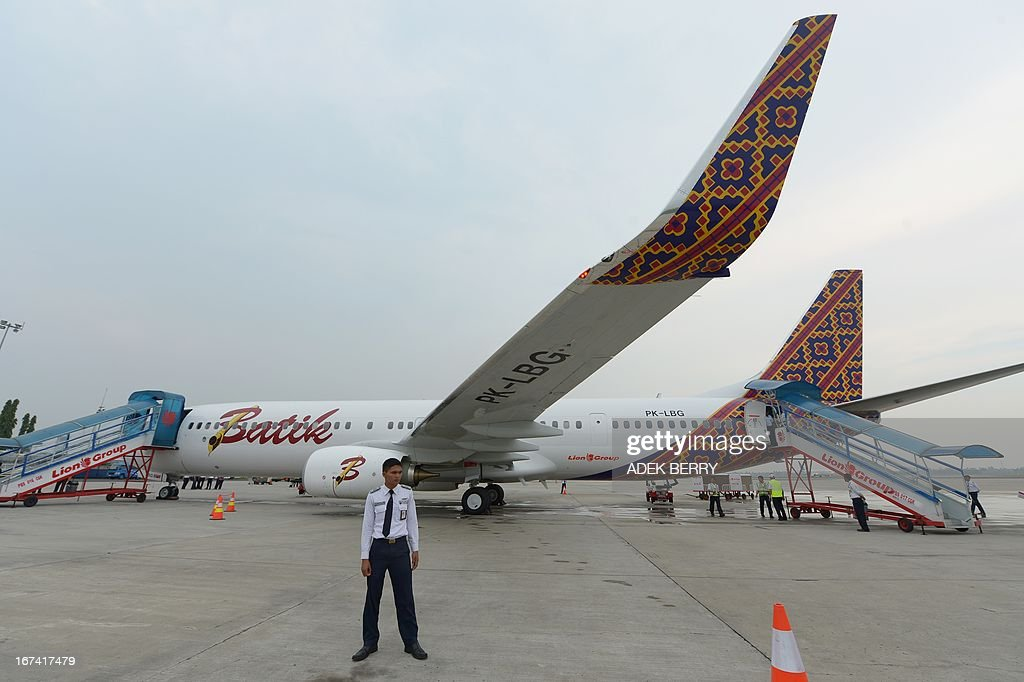 An Indonesian security personnel stands guard next to a Boeing 737-900 plane of the new Indonesian airline Batik Air, a subsidiary of Lion Air is parked at the Soekarno-Hatta airport during the lau...