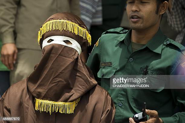 An Indonesian Sharia police officer who will take the role of punisher locally known as 'algojo' armed with a rattan whip prepares for a public...