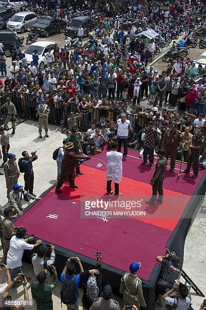 An Indonesian Sharia police whips a man during a public caning ceremony outside a mosque in Banda Aceh capital of Aceh province on September 18 2015...
