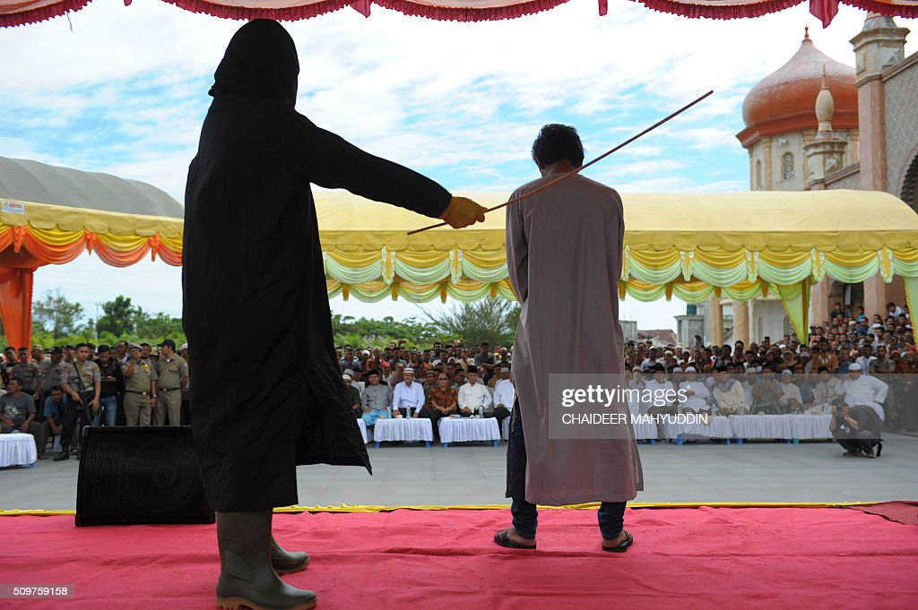 An Indonesian Sharia policeman whips a man and 35 others during a public caning punishment at a Mosque in Meulaboh on the west coast of Aceh province on February 12, 2016. Aceh is the only province in the world's most populous Muslim country that is allowed to implement Islamic Sharia law. AFP PHOTO / Chaideer MAHYUDDIN / AFP / CHAIDEER MAHYUDDIN