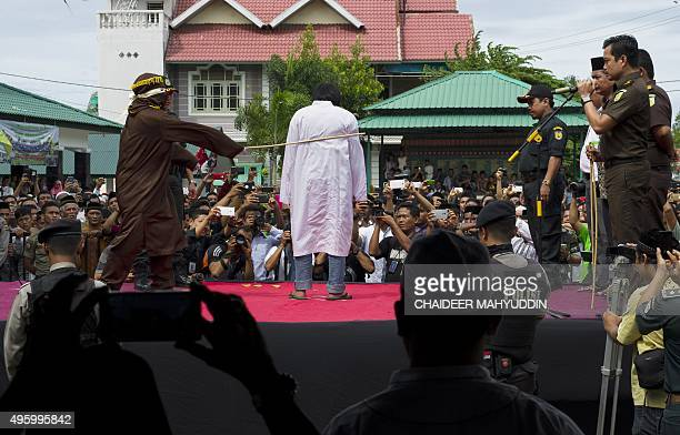 An Indonesian Sharia policeman whips a man during a public caning ceremony in Banda Aceh capital of Aceh province on November 6 2015 Three men...