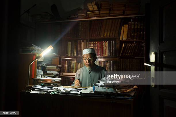 An Indonesian Shariah law professor reads over papers in his office at Abu Bakar Bashir's well known AlMukmin school where numerous Islamic militants...