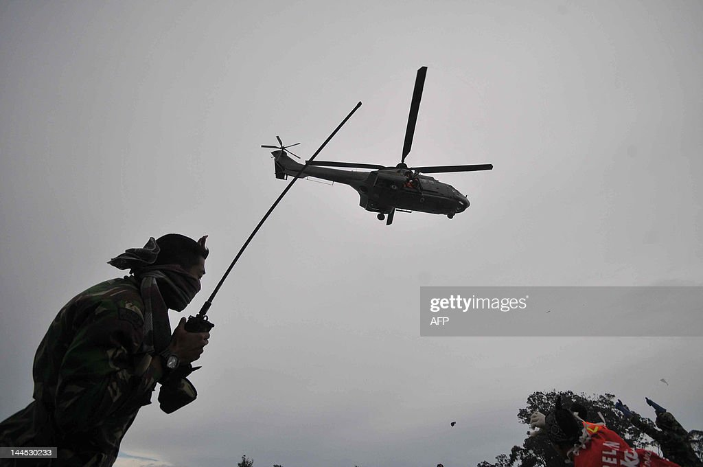 An Indonesian soldier guides a military helicopter to the rescue base on Mount Salak close to the crash site of the Russian Sukhoi Superjet 100 on...