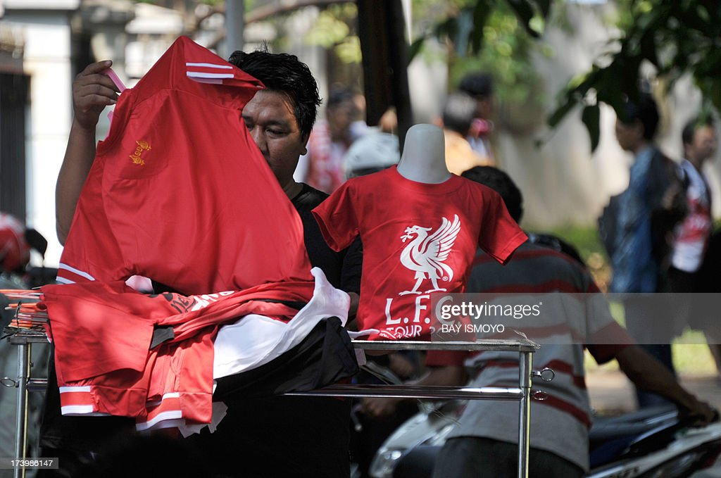 An Indonesian street vendor prepares a Liverpool football jersey for sale before the team's practice session in Jakarta on July 19, 2013. Liverpool will play an Indonesian all-star team on July 20 in an exhibition match. AFP PHOTO / Bay ISMOYO