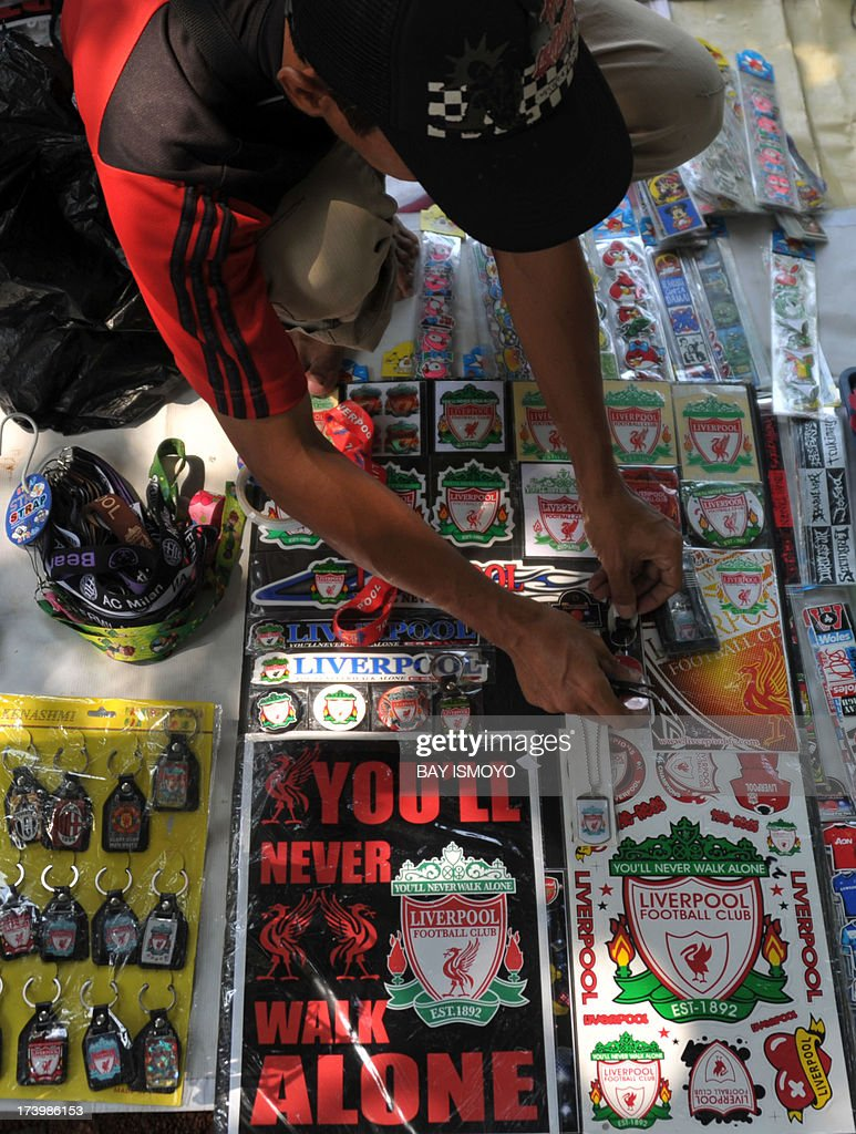 An Indonesian street vendor prepares Liverpool merchandise for sale before the team's practice session in Jakarta on July 19, 2013. Liverpool will play an Indonesian all-star team on July 20 in an exhibition match. AFP PHOTO / Bay ISMOYO
