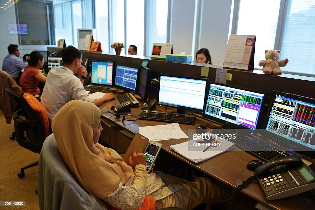 An Indonesian trader (R) checks her tablet computing device during trading at a securities office in Jakarta on February 9, 2016. The Indonesian stock market reopened February 9 while most of the Asian region remained closed for the Lunar New Year holiday, as trading remained thin but dealers took their lead from New York and Europe where banking shares were battered. AFP PHOTO / ADEK BERRY / AFP / ADEK BERRY